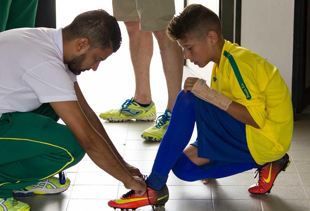 soccer coach tying shoes of brasilian kid