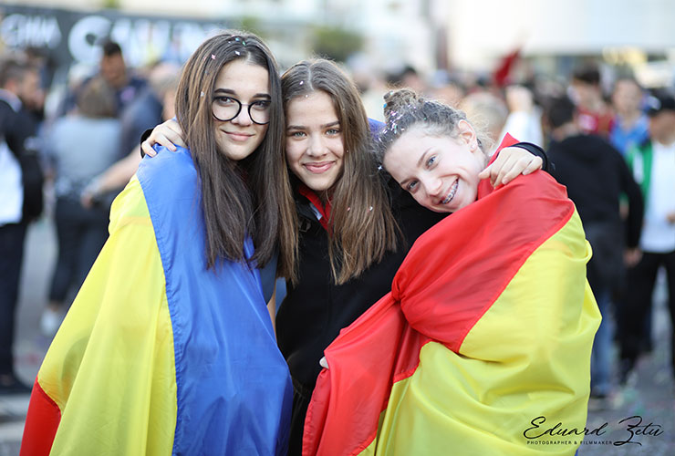 happy girls with big flag of romania